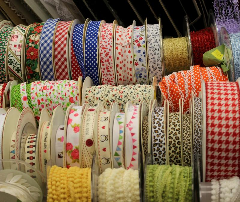 Rows of Ribbon Reels. A colour image of rows of ribbon on reels on display in a crafting and sewing shop stock photos