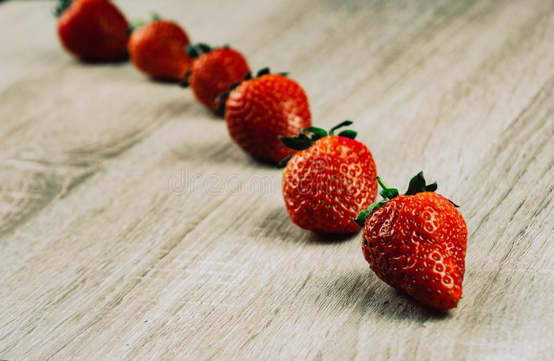 Rows of ripe strawberries on wooden surface. Organic sweet strawberries in rows as a seasonal breakfast. Fresh from a farm stock image