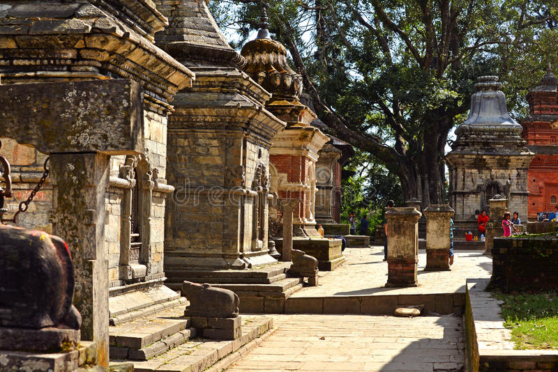 Rows of sacred Hindu temples in Pashupatinath, Nepal. PASHUPATINATH - OCTOBER 8: Unidentified locals visiting the holy Pashupatinath Hindu temples during the royalty free stock photography