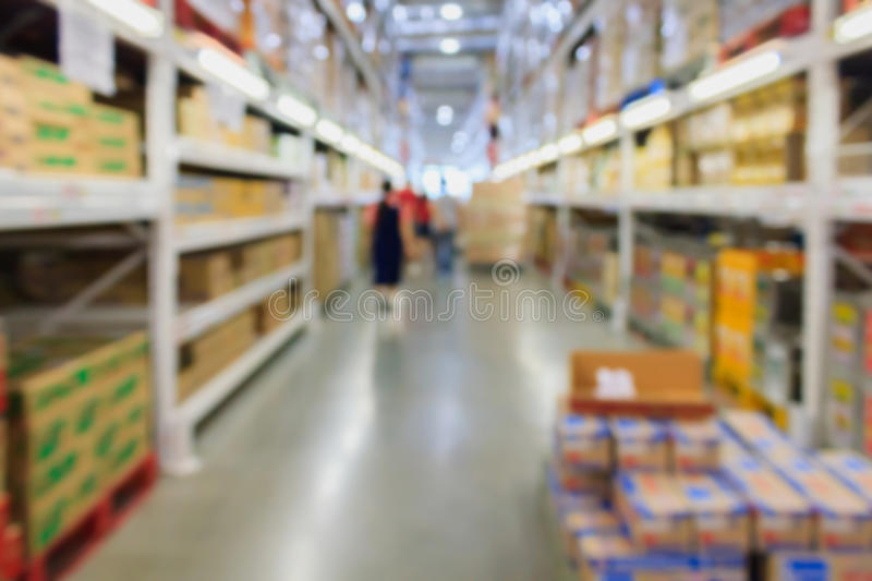 Rows of shelves with boxes in modern warehouse interior stock image