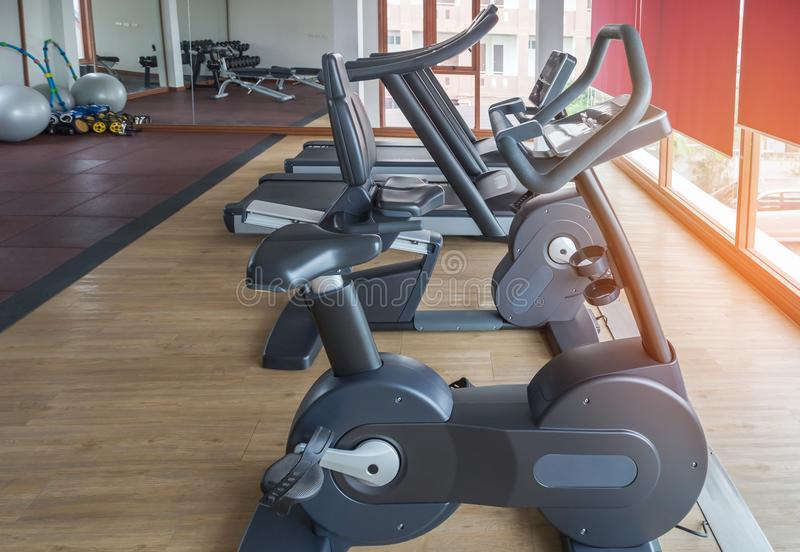 Rows of stationary bikes and treadmills equipment health exercise for bodybuilding. In gym modern fitness center room stock photography