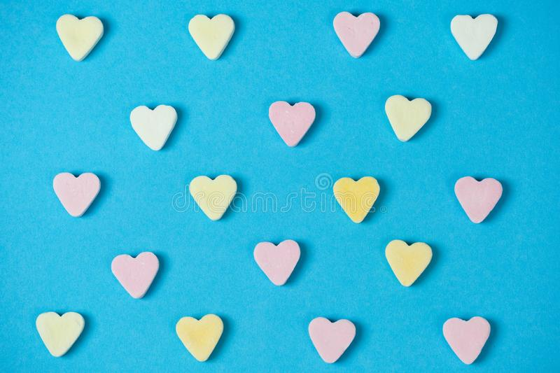 Rows of sugar hearts in a lot of rows on a light blue background stock images