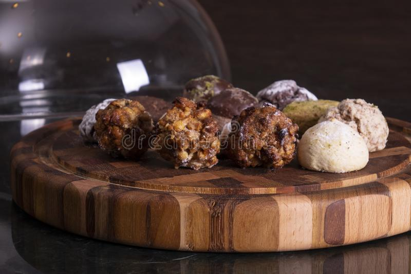Rows of various shortbread and oat cookies with cereals and raisin on black wooden background. Top view. stock images