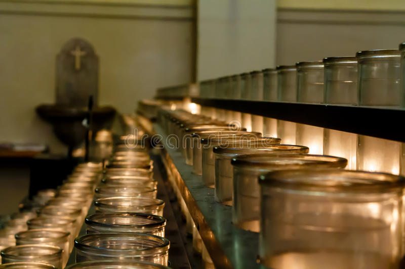 Rows of votive candles lit by churchgoers in Catholic Cathedra stock photos