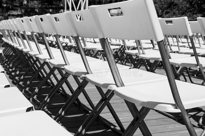 Rows of the white chairs. Minimalistic picture of rows of white empty folding chairs in a summer theatre royalty free stock photos