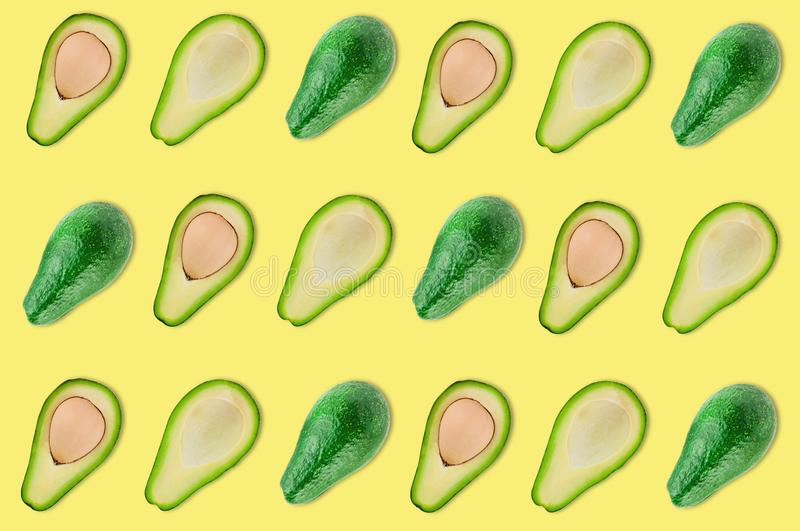 Rows of whole and halves of organic avocado with and without kernels in center of yellow table in kitchen or market stock photography