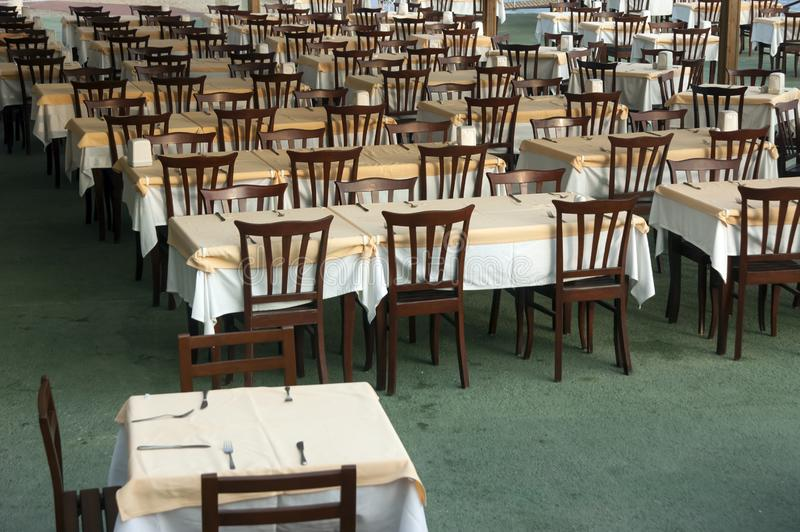 Rows of wooden tables and chairs in the restauran. T are covered with a tablecloth royalty free stock images