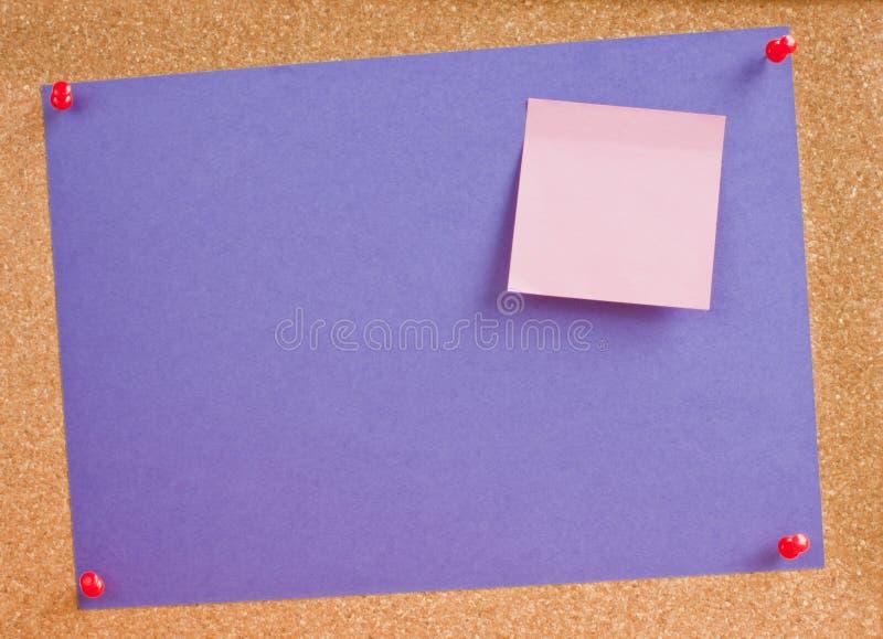Roxo da nota de post-it da placa da cortiça foto de stock