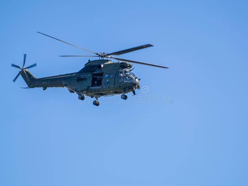 Royal Air Force Helicopter over Hutton. A Royal Air Force helicopter flies over my garden in Hutton, Lancashire at close range complete with large caliber gun stock photos