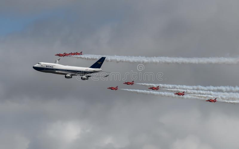 Royal Air Force Red Arrows Display Team in formation with a British Airways Boeing 747 royalty free stock image