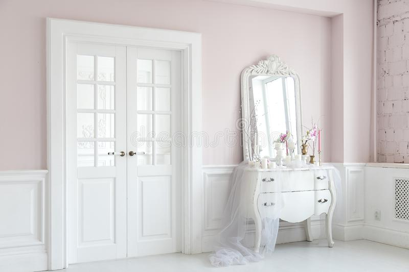 Royal bedroom. Place for make-up girls. Elegant white dressing table with mirror in light classic luxury interior. royalty free stock image