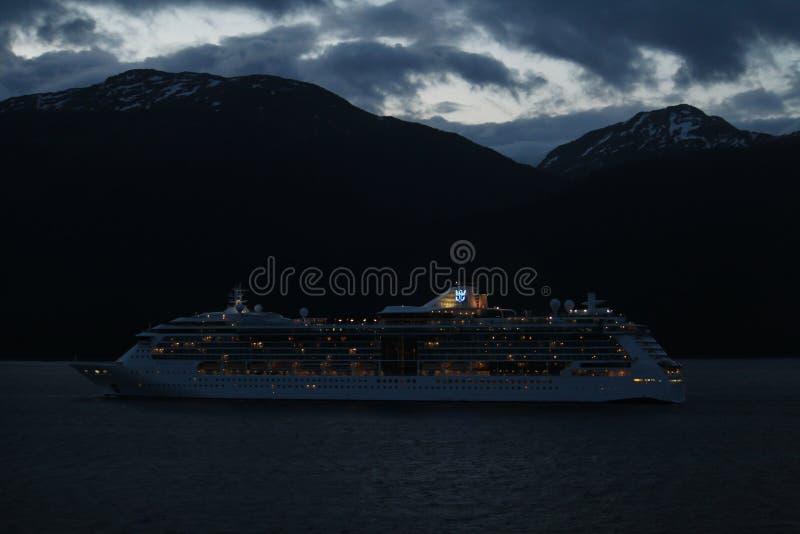 Royal Caribbean kryssningskepp på natten som kryssar omkring längs Alaskianen Mountians royaltyfria bilder