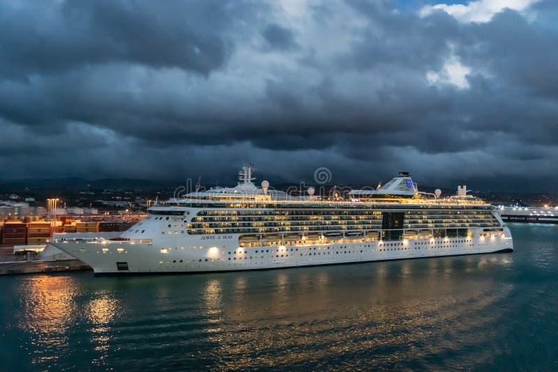 Royal Caribbean kryssningslinjejuvel av havskryssningskeppet som anslutas i porten av Rome på en regnig natt royaltyfria bilder