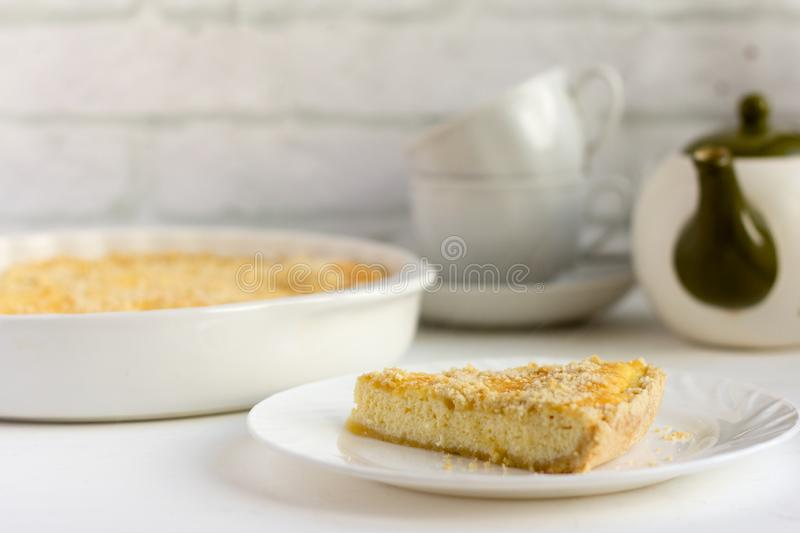 Royal cheesecake, delicious fresh cottage cheese cake with shortbread cookies and tea utensils on the table royalty free stock photos