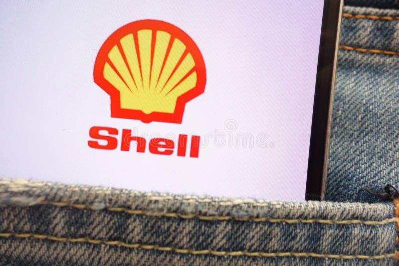 Royal Dutch Shell-embleem op smartphone wordt getoond in jeanszak die wordt verborgen stock fotografie