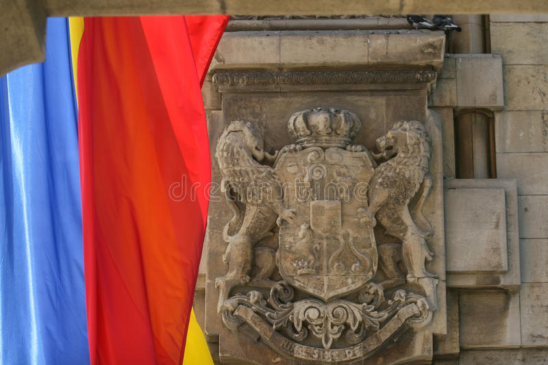 Royal emblem of Romania and Romanian flag royalty free stock photo
