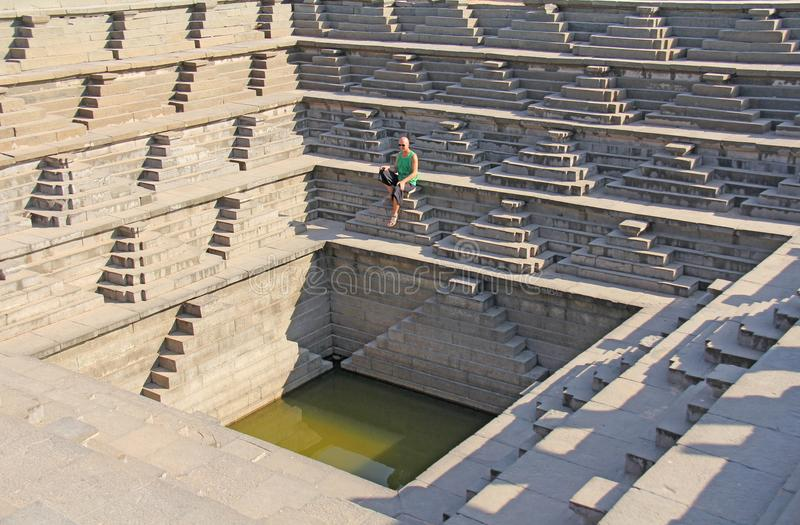 Royal enclosure in Hampi. A young bald man is sitting on the ste stock photography
