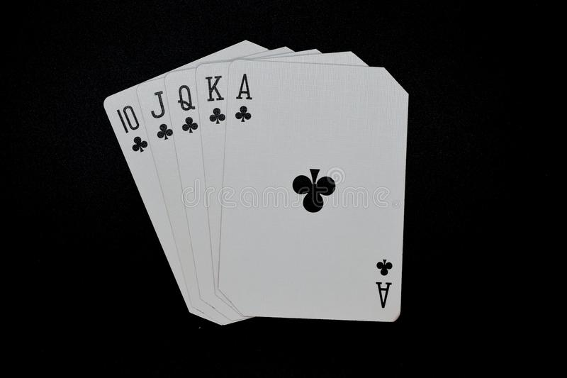 Royal Flush of clubs in poker authentic casino cards game on a black background stock photo