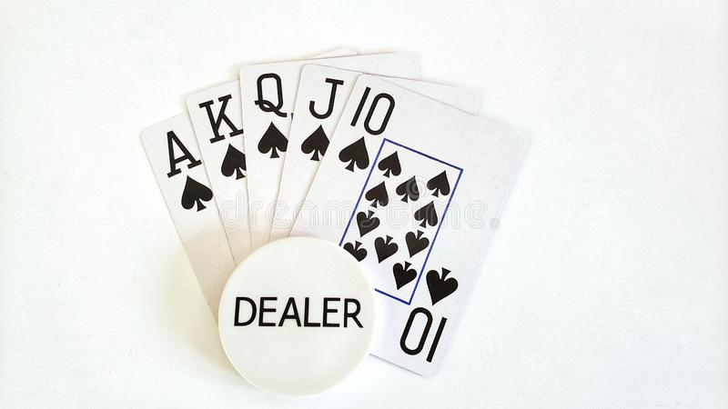 Royal Flush poker hand and dealer button. Playing cards form a Royal Flush poker hand with a dealer button on a white background stock photography