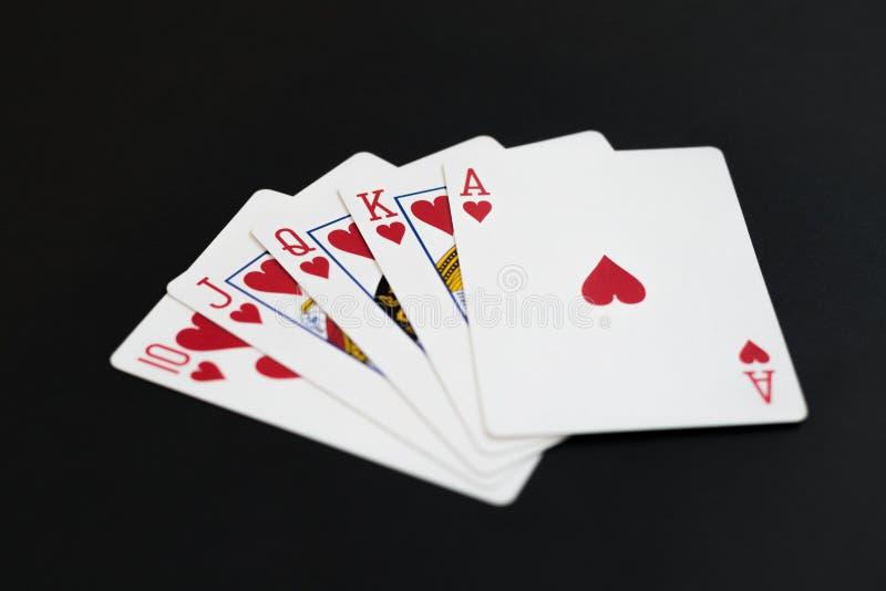 Royal Flush von Herzen im PokerKartenspiel auf einem schwarzen Hintergrund lizenzfreie stockbilder