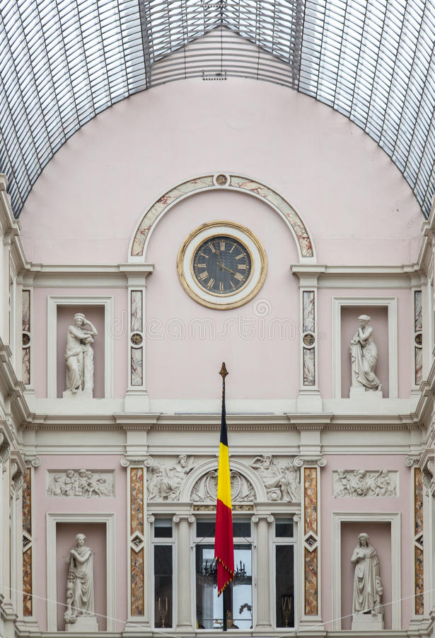 Royal Galeries of Saint Hubert Brussels Belgium. Detail of the Royal Galeries of Saint Hubert in downtown Brussels, Belgium. A clock, a flag, and four statues on royalty free stock photography