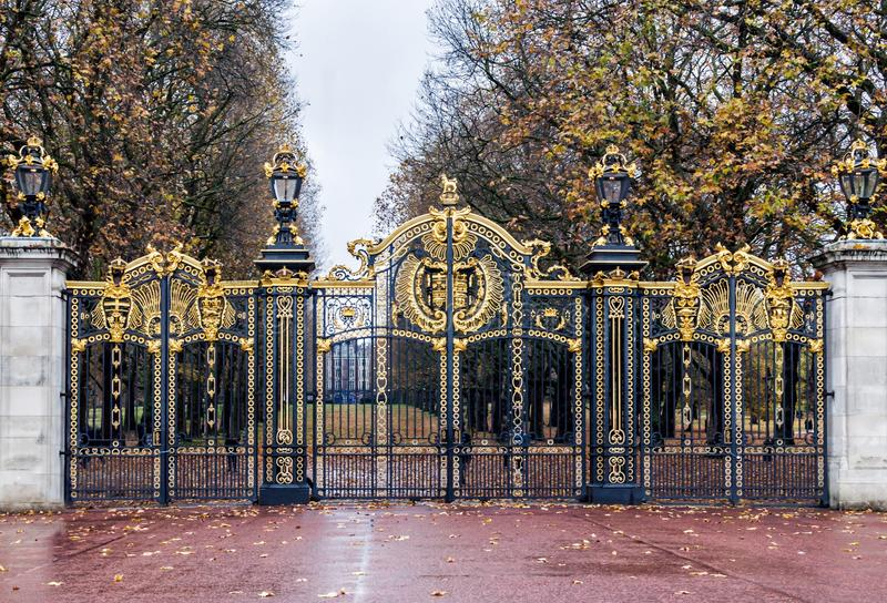 Royal gate of Buckingham Palace in London, United KIngdom. Royal gate of Buckingham Palace at park side in sunny autumn day. Yellow autumn leaves on the tree royalty free stock photo