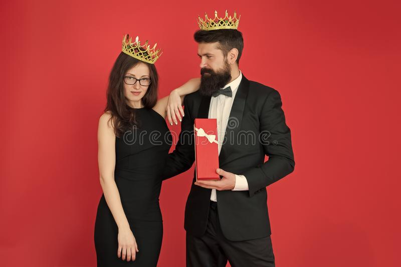 Royal gift. Queen of his heart. Man bearded king in tuxedo golden crown giving gift box to woman elegant dress. Royal royalty free stock photo