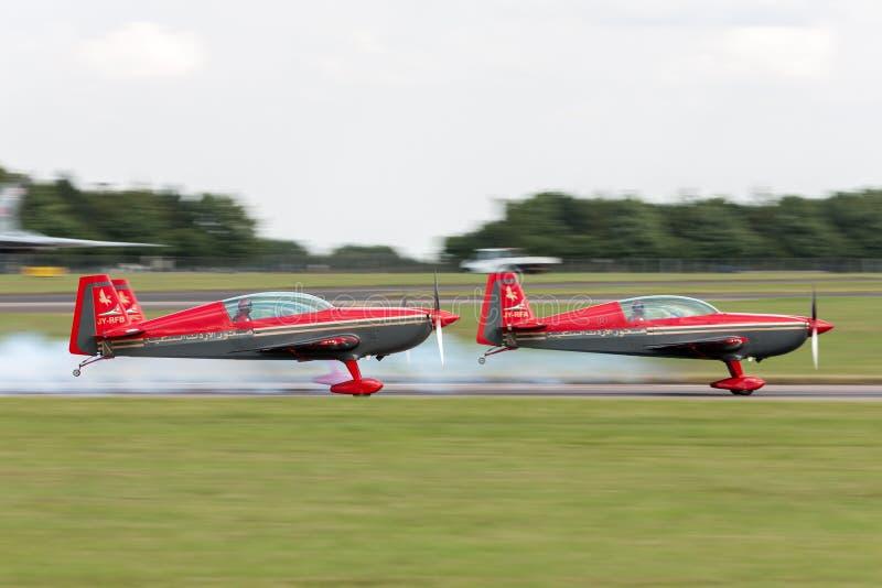 Royal Jordanian-stijgt het Falcons aerobatic team Extra ea-300L jy-RFB in vorming voor een vertoning op royalty-vrije stock afbeelding