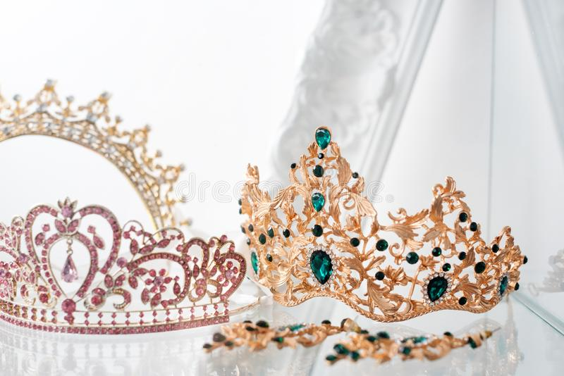 Royal luxury gold and silver crowns decorated with precious stones. Diamond tiaras with gemstones for prom and wedding royalty free stock images