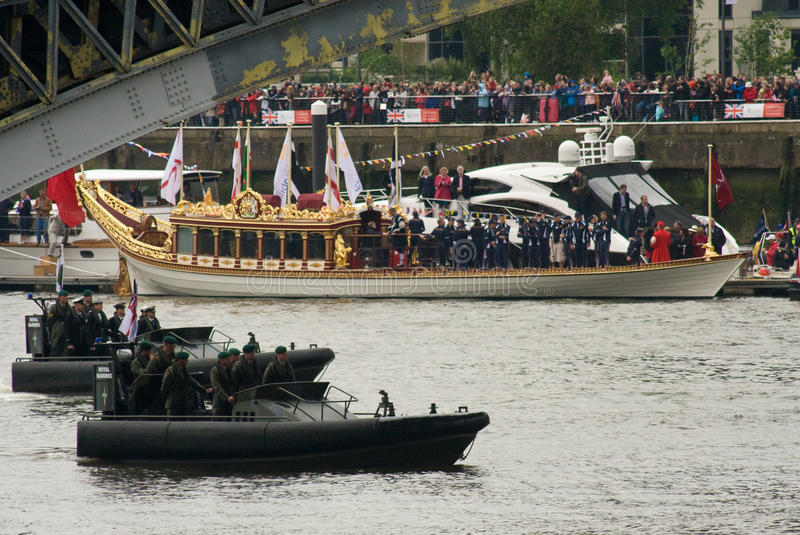 The Royal Marines and the Royal Barge, Gloriana. Royal Marines Commandos pass the Royal Barge, Gloriana, at the Thames Diamond Jubilee Pageant stock images