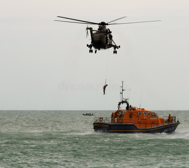 Royal Navy & RNLI Rescue at Airbourne 2015. EASTBOURNE, ENGLAND - AUGUST 16: Royal Navy Sea King and RNLI Lifeboat resue at the Eastbourne Airshow , Airbourne stock image
