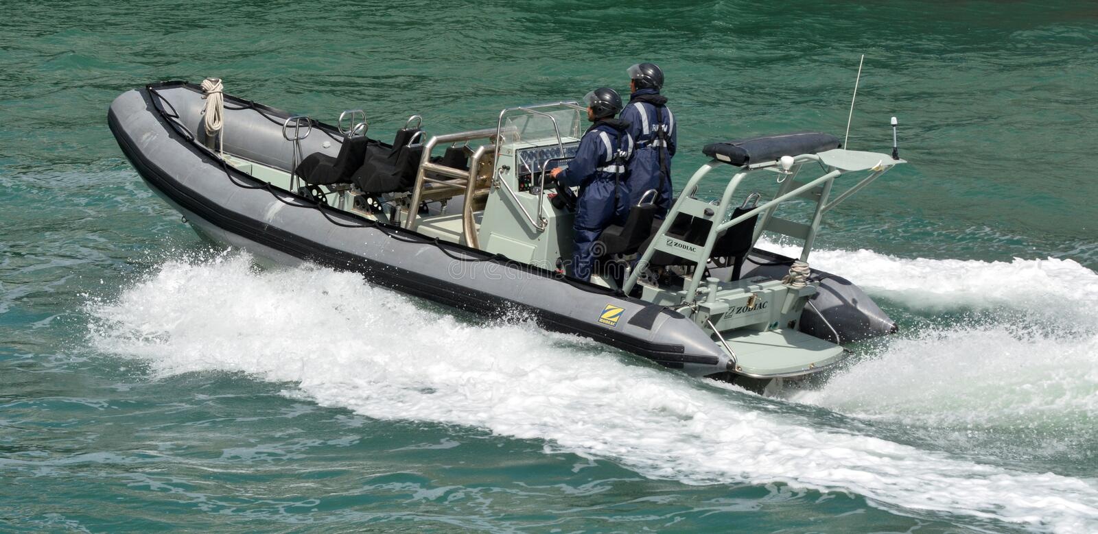 Royal New Zealand navy sailors ride a Zodiak Rigid-hulled inflatable boat in ports of Auckland stock photography