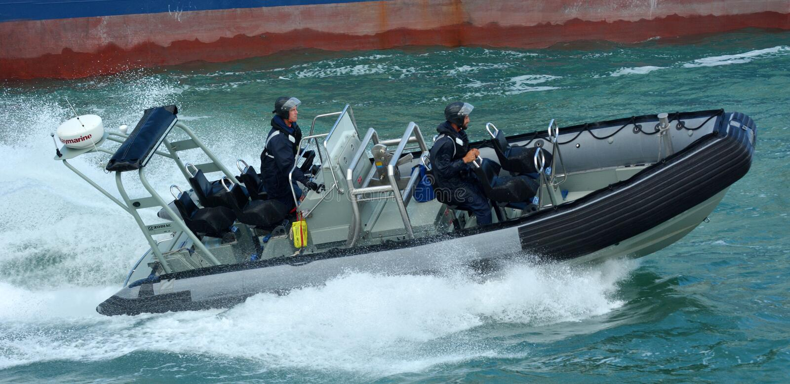 Royal New Zealand navy sailors ride a Zodiak Rigid-hulled inflatable boat in ports of Auckland. AUCKLAND, NZL - JAN 30 2016:Royal New Zealand navy sailors ride a royalty free stock photos