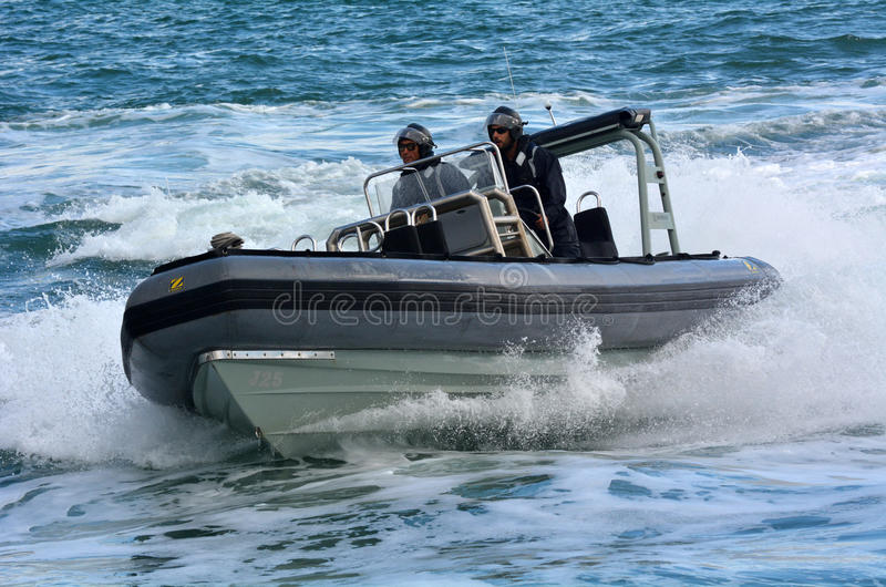 Royal New Zealand navy sailors ride a Zodiak Rigid-hulled inflatable boat in ports of Auckland royalty free stock photography
