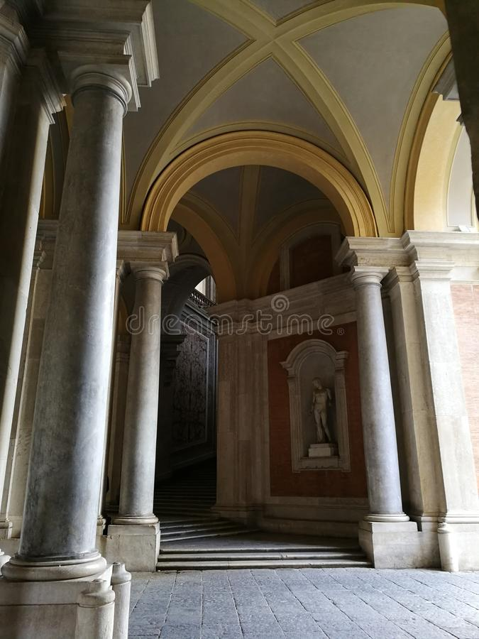 Royal Palace of Caserta - A glimpse of the side access to the Honor staircase. Caserta, Campania, Italy - 3 February 2019: Perspective view of the small access royalty free stock images