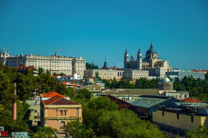 Royal Palace et Almudena Cathedral avec des bâtiments parmi des arbres à Madrid photos stock