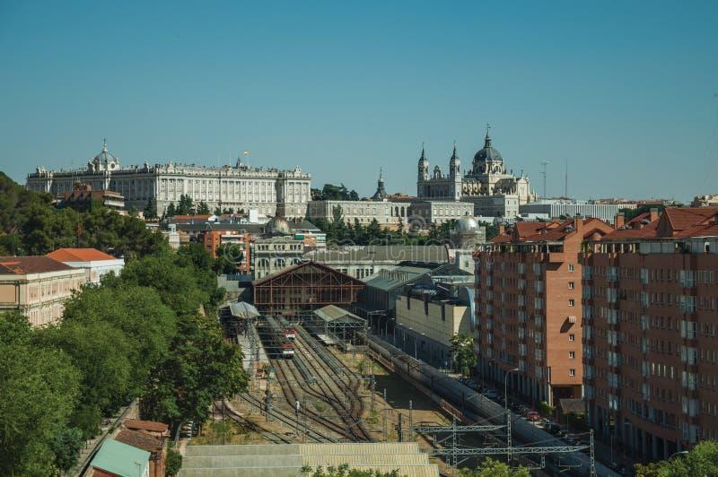 Royal Palace et une station de train avec des rails parmi des bâtiments à Madrid photos libres de droits