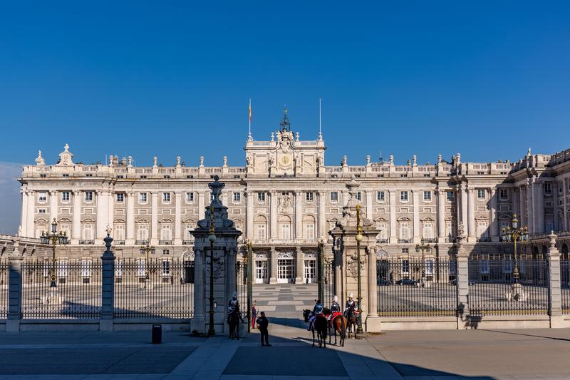 The Royal Palace in Madrid Spain with guards. Madrid, Spain - November 29, 2018: The Royal Palace in Madrid at a cold sunny autuum day, with guards on horseback royalty free stock photo