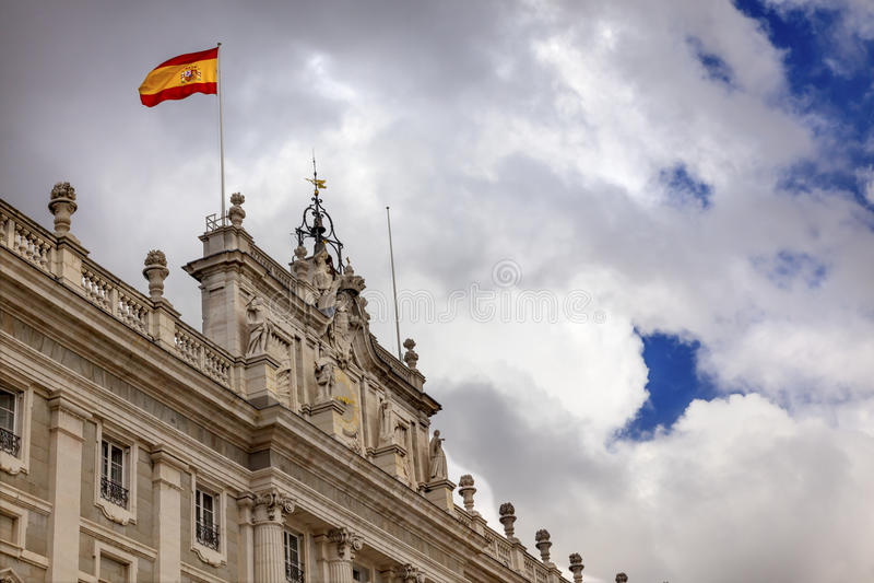 Royal Palace se nubla la bandera española Madrid España del paisaje urbano del cielo fotografía de archivo