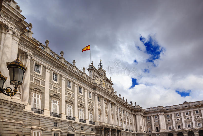Royal Palace se nubla la bandera española Madrid España del paisaje urbano del cielo imagen de archivo libre de regalías