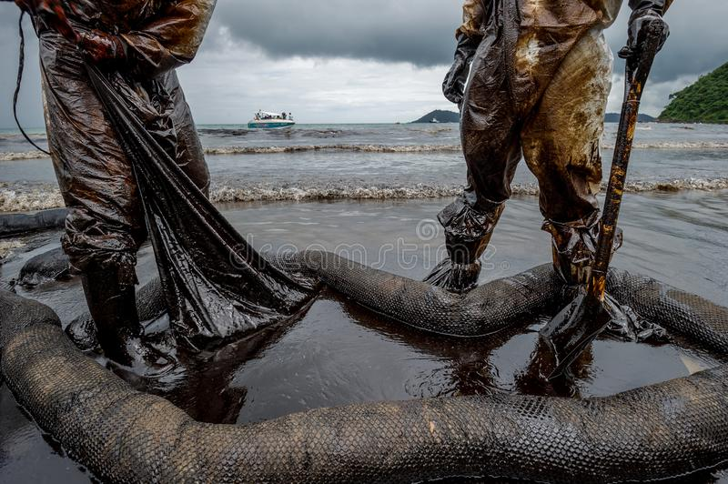 Royal Thai Navy and local volunteers cleaning up a beach from a oil slick on Ao Phrao beach on Samed Island, rayong, Thailand. An. Oil leak from a pipeline stock image