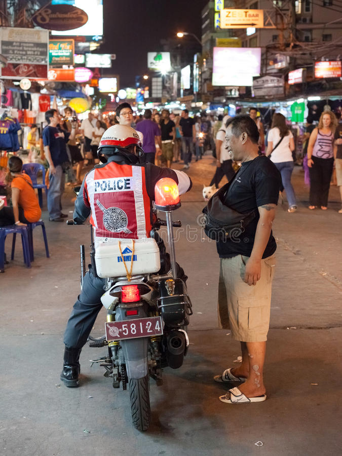 Royal Thai Police. BANGKOK, THAILAND - JANUARY 9, 2012: Local man talks on the street with policeman on the motorcycle on Khao San Road. Royal Thai Police counts stock images