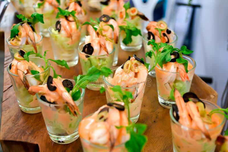 Royal tiger prawn snacks. Shrimps, greens, olives dressing appetizer in glasses shots. Fresh seafood catering service royalty free stock photos