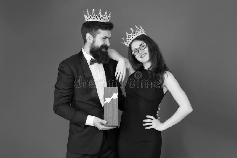 Royal traditions. Celebrate anniversary. Royal gift. King in tuxedo golden crown giving gift box to queen of his heart. Couple in love royal family. Elite royalty free stock image