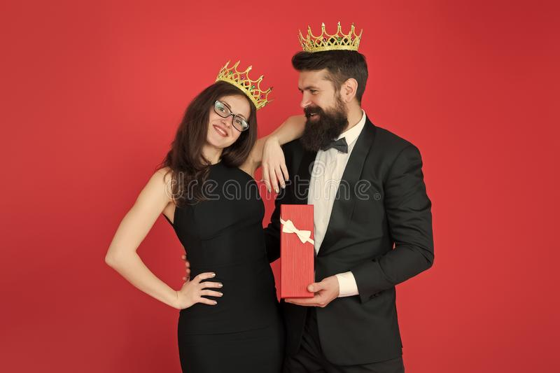 Royal traditions. Celebrate anniversary. Royal gift. King in tuxedo golden crown giving gift box to queen of his heart. Couple in love royal family. Elite stock images