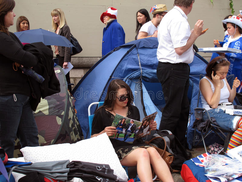 Royal Wedding fan camp. A female fan of the royal wedding between Prince William and Kate Middleton waiting for the big event and reading the latest news about stock photography