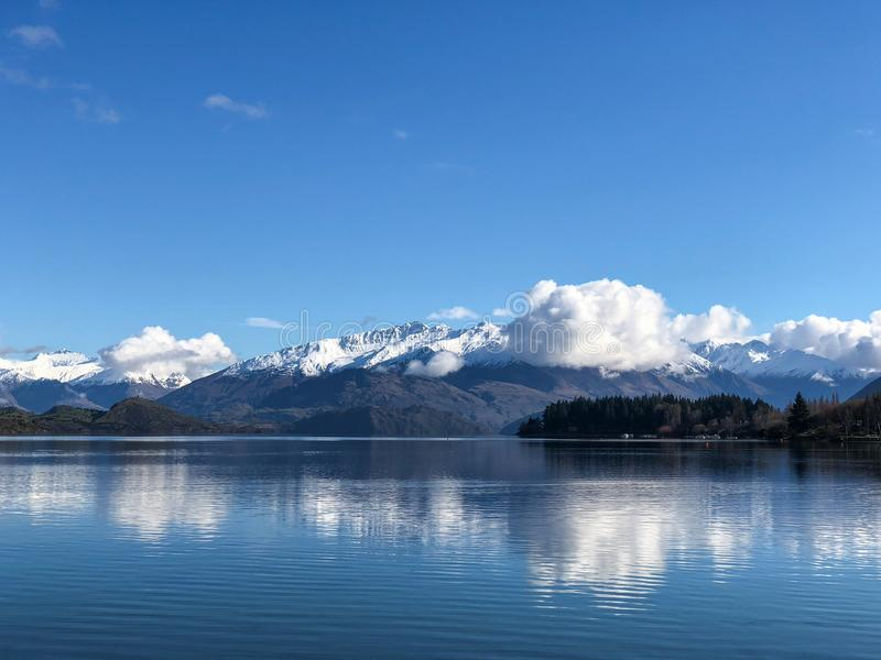 Roys bay at Wanaka in New Zealand with snow capped mountains and clouds in view royalty free stock images
