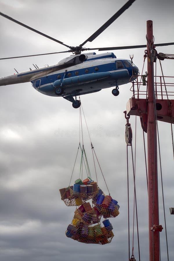 Rozładowywać wyprawa statek opierającym się helikopterem obrazy stock