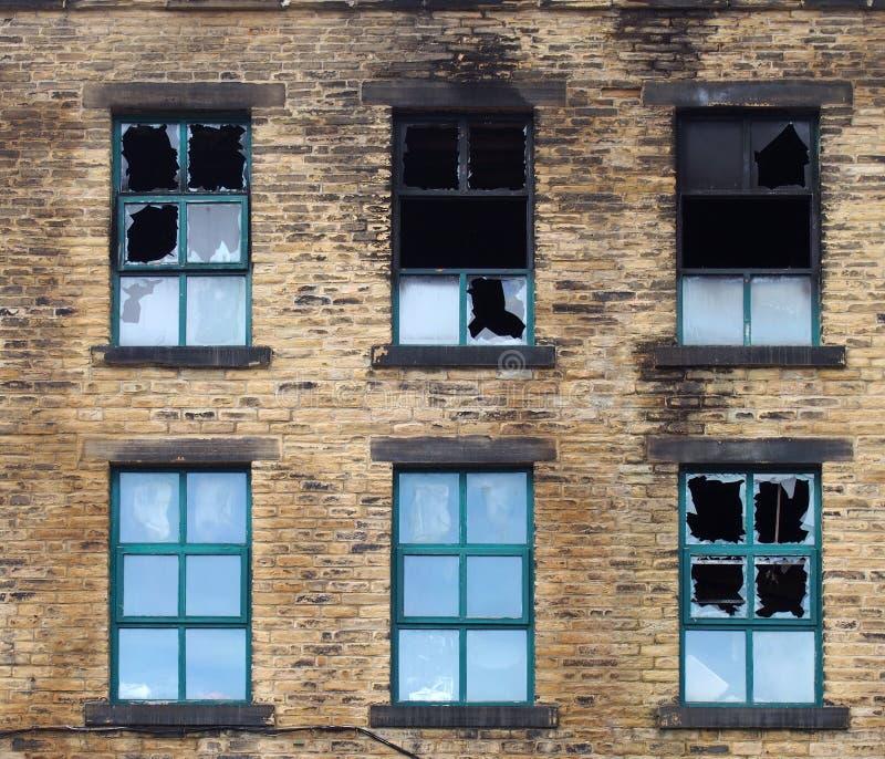 rozbite okna w dużym spalonym starym budynku przemysłowym po pożarze zdjęcie stock