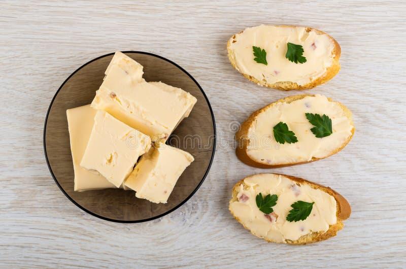 Rozciekły ser z bekonem w talerzu, kanapkach z serem i pietruszce na stole, Odgórny widok zdjęcia royalty free
